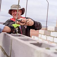 John Rosin fastens rebar into new cinderblock construction at the Uranium Capital Speedway in Milan Saturday.