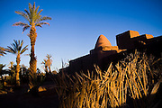 Sunset illuminates the dome roof of a Marabout, or tomb of a venerated saint, in Ait Bounou, an ancient kasbah, or fortified village, in the Moroccan Sahara. The town is quickly falling into ruin as the inhabitants flee the drying well and the advancement of the dunes expedited by a 16-year drought and the damming of the Draa River.