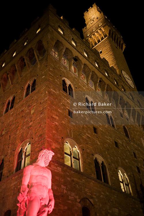 Fountain of Neptune statue in pink lighting in Piazza della Signoria..