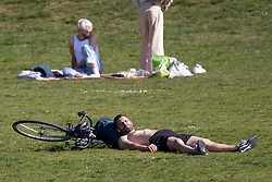 © Licensed to London News Pictures. 23/04/2021. London, UK. A man sunbathes as members of the public relax and enjoy the sunny weather in Greenwich Park in south east London. Temperatures are expected to rise with highs of 16 degrees forecasted for parts of London and South East England today . Photo credit: George Cracknell Wright/LNP