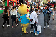 Tourists in Chinatown have their photo taken with a Pokemon Pikachu character in London, England, United Kingdom. The present Chinatown is in the Soho area occupying the area in and around Gerrard Street. It contains a number of Chinese restaurants, bakeries, supermarkets, souvenir shops, and other Chinese-run businesses and is in itself a major tourist destination. Pikachu are a species of Pokemon, fictional creatures that appear in an assortment of video games, animated television shows and movies, trading card games, and comic books licensed by The Pokémon Company, a Japanese corporation.