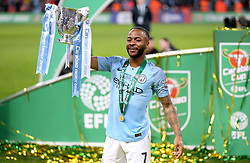 Manchester City's Raheem Sterling holds the trophy after winning the Carabao Cup Final at Wembley Stadium, London.