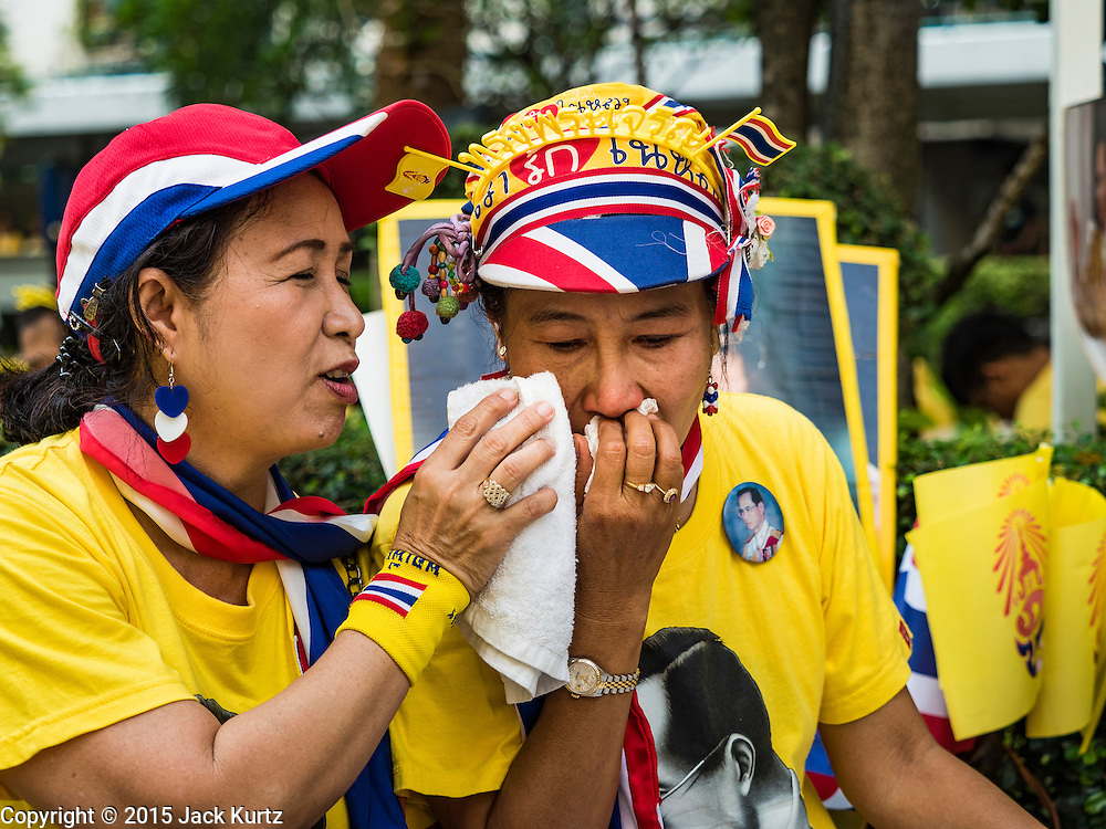 """05 DECEMBER 2015 - BANGKOK, THAILAND:  A woman weeps after shouting """"Long Live the King"""" in the plaza at Siriraj Hospital on the 88th birthday of Bhumibol Adulyadej, the King of Thailand. Hundreds of people crowded into the plaza hoping to catch a glimpse of the revered Monarch. The King has lived at Siriraj Hospital off and on for more than four years.    PHOTO BY JACK KURTZ"""