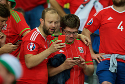 LILLE, FRANCE - Friday, July 1, 2016: Wales supporters check their phones as they celebrate the 3-1 victory against Belgium at full time after the UEFA Euro 2016 Championship Quarter-Final match at the Stade Pierre Mauroy. (Pic by Paul Greenwood/Propaganda)