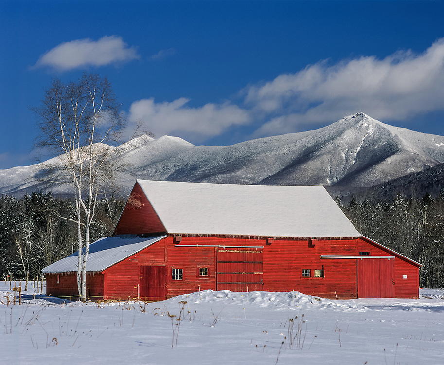 Red barn & sheds with snow covered Franconia Ridge, blue sky & clouds in winter, Grafton County, NH