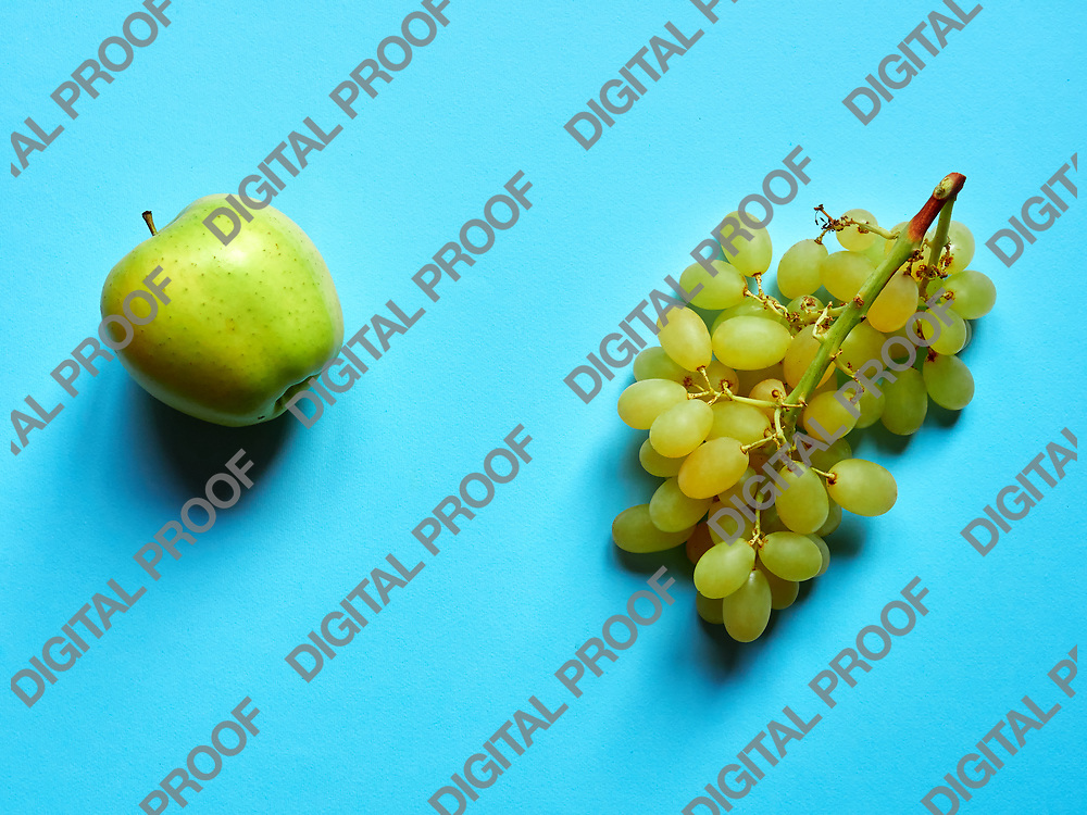 Green apple and bunch of green grapes isolated in studio against a blue background viewed from above