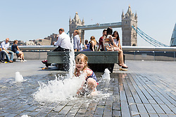 © Licensed to London News Pictures. 26/05/2017. LONDON, UK.  Monica, aged 3 plays in the water fountain on the south bank near Tower Bridge at lunchtime, whilst office workers relax on their lunchbreak. The capital has experienced another day of hot and sunny weather. Photo credit: Vickie Flores/LNP