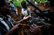 """""""Arrow boys"""" look over the burnt home of a widow that was wounded during a recent LRA attack."""