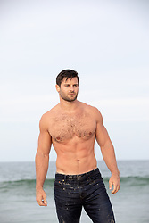 shirtless muscular man in jeans at the ocean