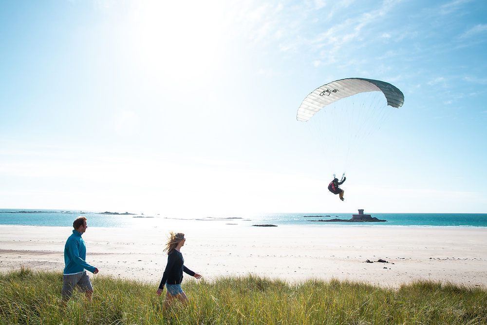 Couple walking through the sand dunes at St Ouen's Bay, Jersey, watching a paraglider descending over the landmark and heritage site, La Rocco Tower.