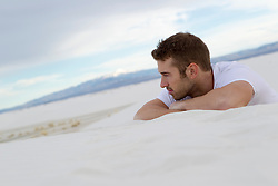 man resting on a sand dune in White Sands, New Mexico