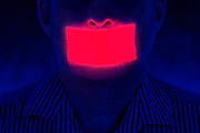 A man with a glowing piece of tape across his mouth. Blacklight photography.