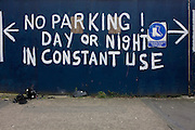 No Parking request between arrows and painted on construction hoarding in south London.