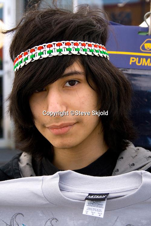 Teenage Hispanic shirt vendor age 17 holding a t-shirt for sale. Cinco de Mayo Fiesta St Paul Minnesota USA