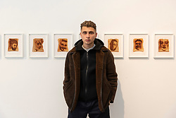 © Licensed to London News Pictures. 06/06/2019. London, UK. 22 year old artist, model and skateboarder Blondey with his artwork titled Epiphanies featuring the famous faces of a series of 25 laser etched portraits on toast showing at The Ronchini Gallery.<br /> Photo credit: Ray Tang/LNP