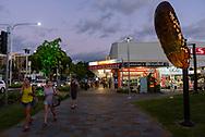 Pedestrians walk at sunset in Cairns, Queensland, Australia