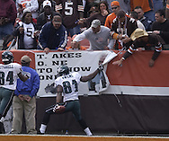 Terrell Owens of Philadelphia rips down a banner at Cleveland Browns Stadium after scoring a touchdown.