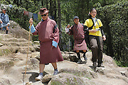 Two Bhutan guides in traditional dress accompany a group of Japanese tourists on their way down from the Tiger's Nest Buddhist temple perched high up, and almost inaccessible except for a steep 3 hour climb, Paro, Bhutan..Bhutan the country that prides itself on the development of 'Gross National Happiness' rather than GNP. This attitude pervades education, government, proclamations by royalty and politicians alike, and in the daily life of Bhutanese people. Strong adherence and respect for a royal family and Buddhism, mean the people generally follow what they are told and taught. There are of course contradictions between the modern and tradional world more often seen in urban rather than rural contexts. Phallic images of huge penises adorn the traditional homes, surrounded by animal spirits; Gross National Penis. Slow development, and fending off the modern world, television only introduced ten years ago, the lack of intrusive tourism, as tourists need to pay a daily minimum entry of $250, ecotourism for the rich, leaves a relatively unworldly populace, but with very high literacy, good health service and payments to peasants to not kill wild animals, or misuse forest, enables sustainable development and protects the country's natural heritage. Whilst various hydro-electric schemes, cash crops including apples, pull in import revenue, and Bhutan is helped with aid from the international community. Its population is only a meagre 700,000. Indian and Nepalese workers carry out the menial road and construction work.