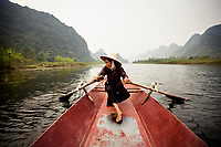 A woman paddles a small boat along the Day River in Hanoi, Vietnam, on her way toward the Perfume Pagoda.