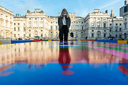 © Licensed to London News Pictures. 14/10/2021. LONDON, UK. A staff member views Lakwena Maciver's Basketball Court paintings in the courtyard of Somerset House. Preview of 1-54 Contemporary African Art Fair, the leading international art fair dedicated to contemporary art from Africa and its diaspora.  Works by around 48 exhibitors are on show in a show which runs 14 to 17 October at Somerset House.  Photo credit: Stephen Chung/LNP