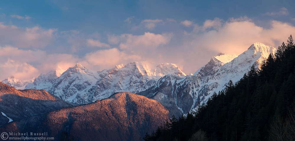The peaks of the Cheam Range.  From left to right: Cheam, Lady, Baby Munday, Stewart and Welch Peaks. While Cheam Peak (aka Mount Cheam) is often the most visible, Welch Peak is actually the highest peak in the Cheam Range.  Photographed from Harrison Lake in Harrison Hot Springs, British Columbia, Canada