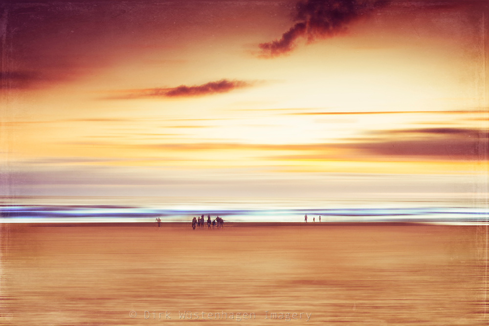 Abstract beach scenery with people enjpoing the sun setting over the Atlantic.