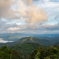 """Panoramic rainy season view of the higher elevations of Kaeng Krachan National Park from Panoenthung. The famous """"Sea of fog"""" is visible in the photograph."""