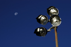 Stadium lighting against a blue sky with the moon in the background