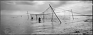 Salmon netters Bob Ritchie (left) and Jim Mitchell closing the pocket after taking out a salmon out of a 'jumper' net at low tide on the sands at Kinnaber, Angus.<br /> Ref. Catching the Tide 35/00/34a (30th May 2000)<br /> <br /> The once-thriving Scottish salmon netting industry fell into decline in the 1970s and 1980s when the numbers of fish caught reduced due to environmental and economic reasons. In 2016, a three-year ban was imposed by the Scottish Government on the advice of scientists to try to boost dwindling stocks which anglers and conservationists blamed on netsmen.