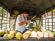 12 MARCH 2014 - BANGKOK, THAILAND:    A coconut vendor cuts open coconuts in the back of his pickup truck. Coconuts, and coconut water have become a very popular natural drink.   PHOTO BY JACK KURTZ