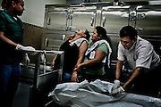 """Wendy Maritza Rodriguez, 38, (left) reacts after she recognized the body of her adopted son with her sister Estela Marisol Rodriguez, 37, (R) at the morgue of the Insituto Medico Legal of San Salvador, El Salvador. August 15, 2012.  Jonathan manuel Peña, 27, a former member of the gang Mara Salvatrucha was shot from the back the night before. He left the mara 6 years ago and had some of his tatoos erased, but for the """"mareros"""" is difficult to leave their past, the gangs have a saying """"o vivis por la mara o moris por la mara"""" """"either you live for the mara or you die for the mara"""" meaning that there is no way out.  Photo/Tomas Munita"""