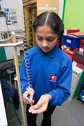 Student carrying out a physics experiment to see why a copper spring stretched more than a steel one,