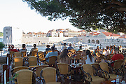 A restaurant cafe with outside seating terrasse in the shade under a tree on the city wall, overlooking the old harbour, Arsenal and Saint John's fortress. People sitting drinking. Dubrovnik, old city. Dalmatian Coast, Croatia, Europe.