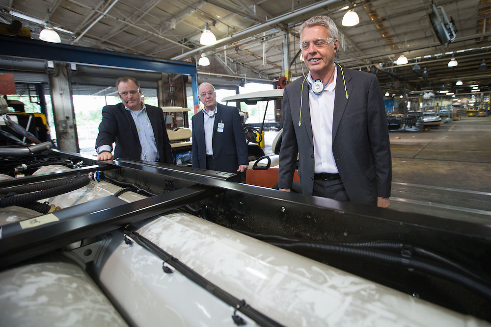 Standing over the gas tank of a school bus along the assembly line, Phil Horlock, right, president and CEO of Blue Bird, smiles during a tour of the company's manufacturing plant on Tuesday, April 14, 2015 in Fort Valley, Ga. Also pictured is John McKowen, left, vice president of manufacturing, and Roy Willis, president and CEO of the Propane Education and Research Council. Photo by Kevin Liles for The New York Times
