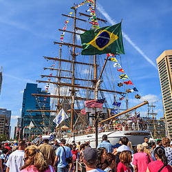 Baltimore, MD, USA - June 16, 2012: Tourists walk past a large ship on a summer day in the Inner Harbor of the City of Baltimore, Maryland.