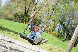 Happy young boy swinging on swing playground