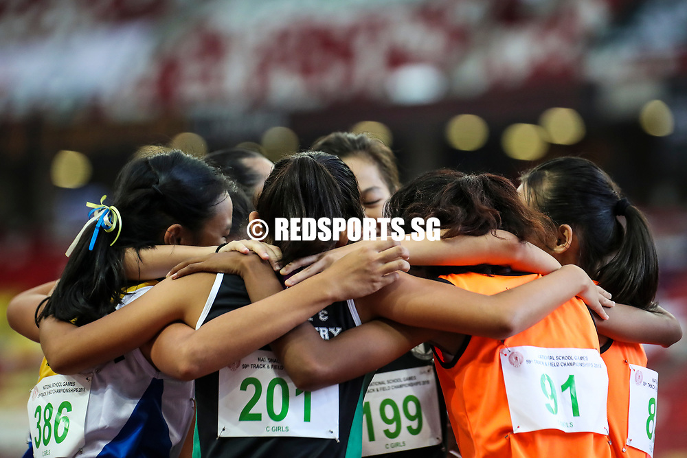 The C Division girls' 100m competitors share a group hug after their final. (Photo © Lim Yong Teck/Red Sports)