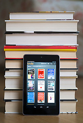 Google Nexus 7 tablet computer with kindle e-book library application and pile of traditional hardback paper books
