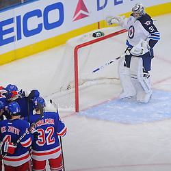 New York Rangers right wing Ryan Callahan (24) celebrates his goal on Winnipeg Jets goalie Ondrej Pavelec (31) with teammates during first period NHL action between the Winnipeg Jets and the New York Rangers at Madison Square Garden in New York, N.Y. The Rangers lead the Jets 1-0 during the first intermission.