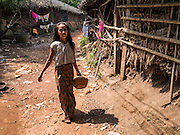 30 OCTOBER 2015 - TWANTE, MYANMAR: A woman carries a half finished piece of pottery through the potters' village in Twante, (also spelled Twantay) Myanmar. Twante, about 20 miles from Yangon, is best known for its traditional pottery. The pottery makers are struggling to keep workers in their sheds though. As Myanmar opens up to outside investments and its economy expands, young people are moving to Yangon to take jobs in the better paying tourist industry or in the factories that are springing up around Yangon.     PHOTO BY JACK KURTZ