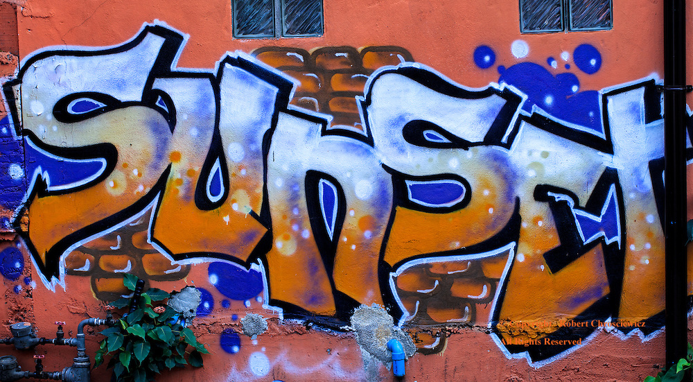 """An Alleys' Sunset View: A wall down a dark back alley is adorned with the bright orange and blue graffiti with the word """"Sunset"""", Chiang Mai Thailand."""