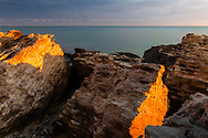 Golden light at sunset ovet the rocks by the sea