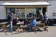 Walking friends enjoy a rest on benches at an outdoor cafe in Epping Forest, Essex, Enghland. The outdoor cafe is in a car park inside Epping Forest, an area of ancient woodland in south-east England, straddling the border between north-east Greater London and Essex. It covers 2,476 hectares and contains areas of woodland, grassland, heath, rivers, bogs and ponds - popular with families and more serious walkers.