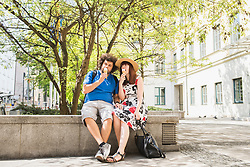 Couple eating ice cream outdoors in city