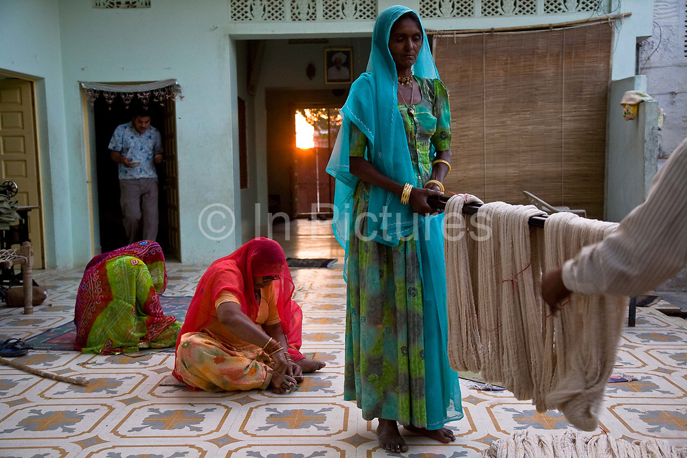 Women dhurrie  (carpet) weavers prepare wool for the dying process in a small family run business, Salawas, Rajasthan, India