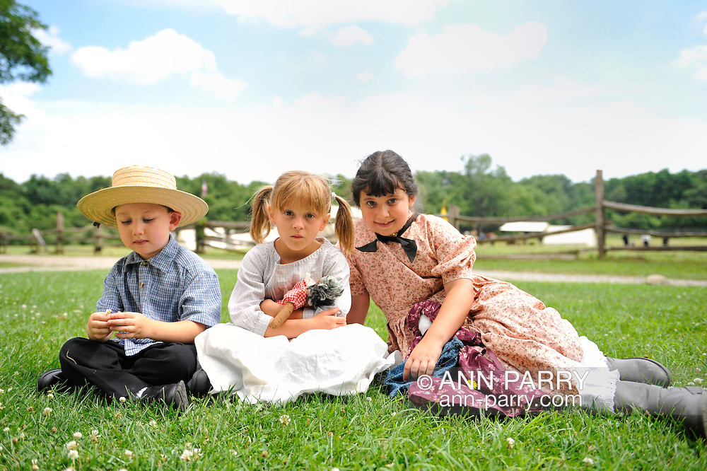 Old Bethpage, New York, USA - July 21, 2012: : ROBERT WALKER, 4, of Coram  (left), JULIAN LYNN ZOLL, 6, of Levittown (center), and MADELYN WALKER, 7, of Coram (right), wear clothes of American Civil War era while portraying family members of Union soldiers at Camp Scott re-creation, at Old Bethpage Village Restoration, to commemorate 150th Anniversary of American Civil War, on Saturday, July 21, 2012.