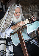 A rabbi at the western wall praying out loud. He reads a siddur (prayerbook) on a shtender that is a lectern used to prop up books at an angle, and allow for easier reading. Traditional shtenders frequently incorporate a locker under the desktop where prayerbooks and study material may be locked when not in use, and many feature a footrest for comfort during extended study sessions or standing prayers.