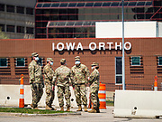 """26 APRIL 2020 - DES MOINES, IOWA: Soldiers with the Iowa Army National Guard wait for people to arrive at the COVID-19 drive through testing site in Des Moines. Iowa started mass testing Saturday, with a drive through testing site in a parking lot in downtown Des Moines. The testing this weekend is considered a """"soft opening"""" for the program and tests were reserved for medical professionals and first responders. Despite numerous outbreaks in meat packing plants throughout Iowa, members of the public have not been able to get tested. On Saturday, 25 April, there were 5,092 confirmed cases of COVID-19 (Coronavirus / SARS-CoV-2) in Iowa (an increase of 647 since Friday, April 24) and 112 deaths in Iowa caused by COVID-19.          PHOTO BY JACK KURTZ"""