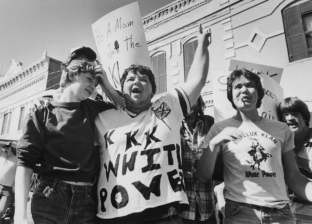 Ku Klux Klan members and supporters jeer and taunt African American civil rights marchers in Monroe, Georgia.
