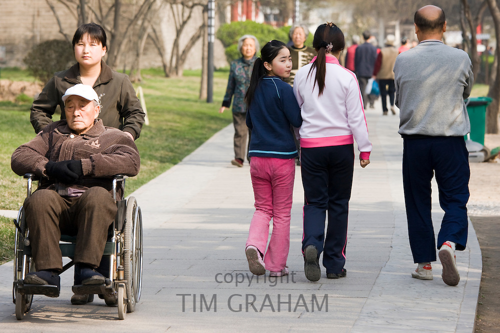 People stroll through park by the City Wall, Xian. China has a one child policy to limit population.